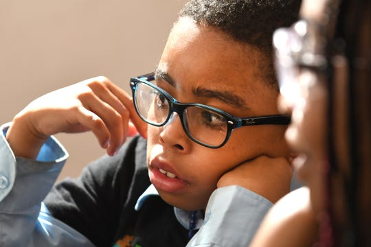 Ryan Cargile, 9, watches his mother Ebony Cargile start his lessons from the Michigan Charter Virtual Academy at their Flint home
