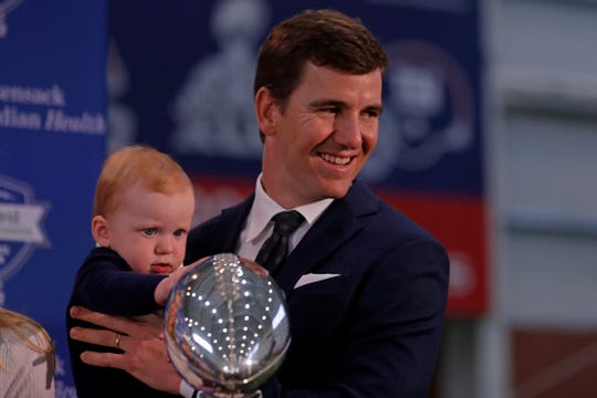 New York Giants NFL football quarterback Eli Manning with his son Charles after announcing his retirement Friday.