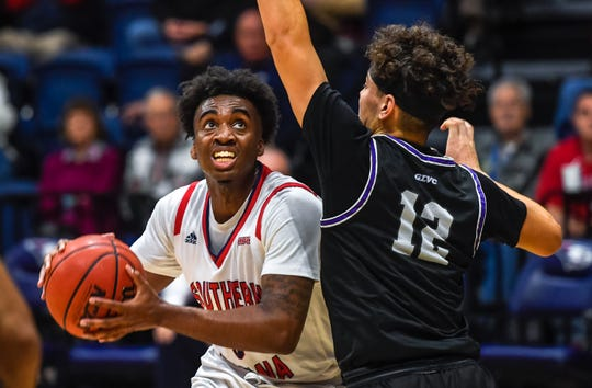 University of Southern Indiana's Kobe Caldwell (0) looks to shoot over defense from Truman's Hunter Strait (12) as the University of Southern Indiana Screaming Eagles play the Truman University Bulldogs at the Screaming Eagle arena Thursday, January 23, 2020.