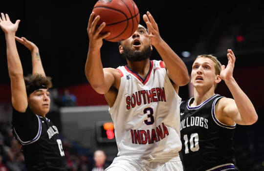 University of Southern Indiana's Mateo Rivera (3) drives past Truman's Hunter Strait (12) and Turner Scott (10) as the University of Southern Indiana Screaming Eagles play the Truman University Bulldogs at the Screaming Eagle arena Thursday, January 23, 2020.