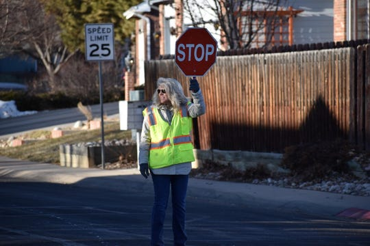 Lopez Elementary principal Traci Gile volunteers as a crossing guard for students headed to school on Friday, Jan. 24, 2020 in Fort Collins, Colo.
