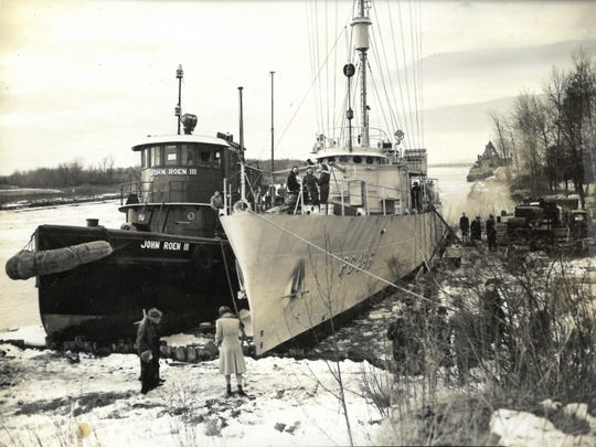 "U.S. Navy World War II patrol ship PC-496 floats next to the John Roen III in the Sturgeon Bay channel. PC-496 was one of the ships built in the city by Leathem D. Smith, and ships built there for the war, and locally built warships are the subject of the new ""Built for Battle"" exhibit at the Door County Maritime Museum."