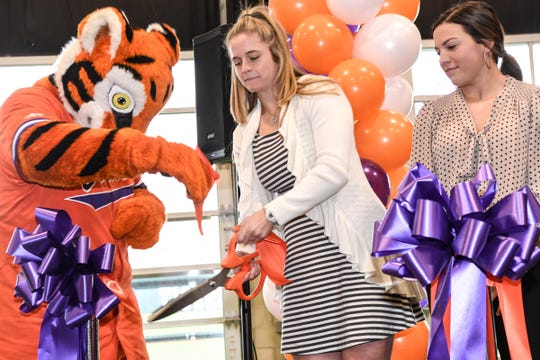 Clemson Tiger holds a piece of ribbon as softball players MK Bonamy cuts a piece near teammate Cammy Pereira inside the Tom Hash Indoor Practice facility. The first home game is February 12, 2:30 p.m. against Western Carolina.