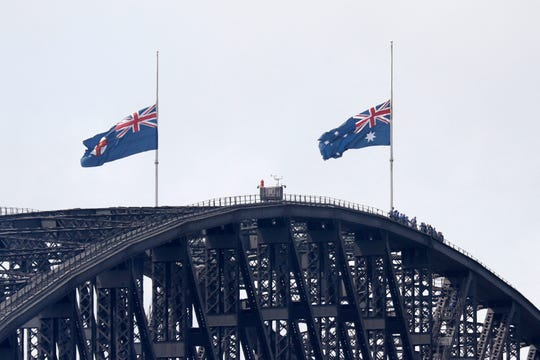 People climbing the Sydney Harbour Bridge stop under flags flying at half-mast as mark of mourning and respect in Sydney, Australia, Friday,, for three U.S. crew members, including a Great Falls man, of an aerial water tanker that crashed Thursday while battling wildfires in Australia.