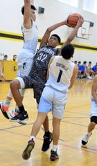 A Pair of Saint Paul Christian School Warriors , in white, defend against Humphreys' Donovan Okpokwasili in Kanto Classic action Jan. 23 in Tokyo, Japan. The Warriors beat Humphreys 36-35.