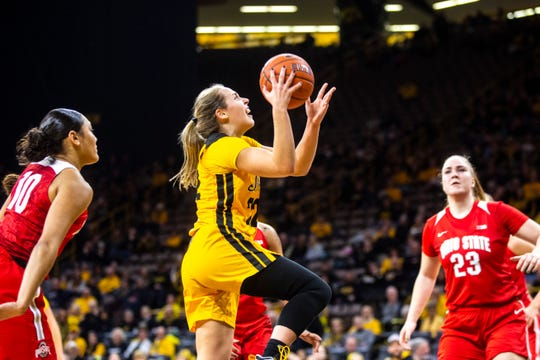 Iowa guard Kathleen Doyle drives to the basket as Ohio State guard Braxtin Miller, left, and forward Rebeka Mikulášiková (23) defend during a NCAA Big Ten Conference women's basketball game, Thursday, Jan. 23, 2020, at Carver-Hawkeye Arena in Iowa City, Iowa.