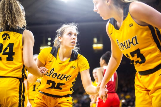 Iowa guard Kathleen Doyle, center, gets helped up by teammates Gabbie Marshall and Amanda Ollinger during a NCAA Big Ten Conference women's basketball game, Thursday, Jan. 23, 2020, at Carver-Hawkeye Arena in Iowa City, Iowa.