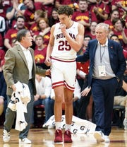 Hoosiers forward Race Thompson (25) walks off the floor with team doctors after hitting his head on the court during the game against Michigan State at Assembly Hall on Thursday.