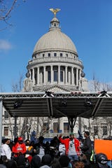 Several hundred people gather in front of the Mississippi Capitol in Jackson, on Friday, Jan. 24, 2020, to protest conditions in prisons where inmates have been killed in violent clashes in recent weeks. Mississippi's new governor says he and the interim corrections commissioner toured a troubled state prison to see conditions and to try to understand what led to an outburst of deadly violence in recent weeks. (AP Photo/Rogelio V. Solis)