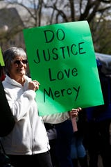 Martha Lightsey of Wesson, Miss., holds a homemade sign calling for justice, love and mercy at a mass gathering in front of the Mississippi Capitol in Jackson, Friday, Jan. 24, 2020, to protest conditions in prisons where inmates have been killed in violent clashes in recent weeks. (AP Photo/Rogelio V. Solis)