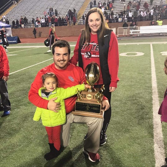 Knoxville Central Bobcats defensive coordinator Nick Craney with his wife, Brooke, and daughter, Lilly, with the 2019 State Championship trophy on Dec. 6, 2019 in Cookeville, Tennessee.