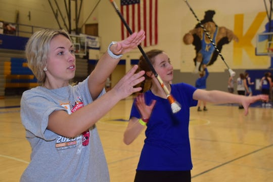 UT head majorette Kaylee Kennedy does neck rolls with Brooklynn Bowman, 14, at the majorette workshop held at Karns High School Monday, Jan. 20.