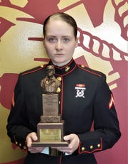 """PFC Miranda Sites poses with the """"Chesty"""" Fuller award after she earned the top honor of company honor graduate, the number one female in her company."""