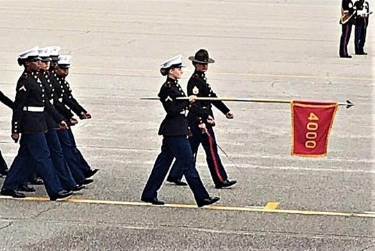 Carrying her platoon's guidon flag, Private First Class Miranda Sites marches with her drill instructor ahead of the platoon during the graduation ceremony.