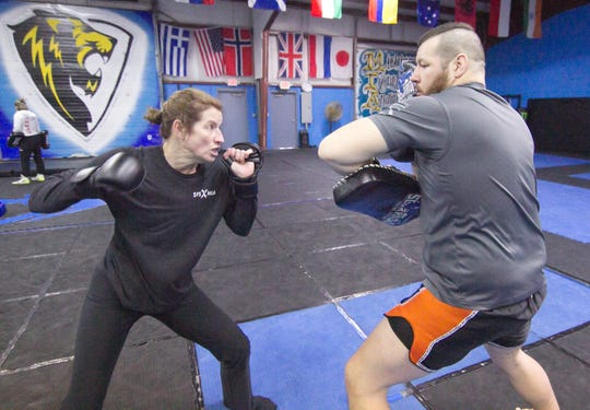 Working with trainer Josh Parisian, right, Heidi Miller prepares on Wednesday, Jan. 22, 2020 at the Michigan Institute of Athletics in Genoa Township for her first mixed martial arts bout, to be held in Walker.