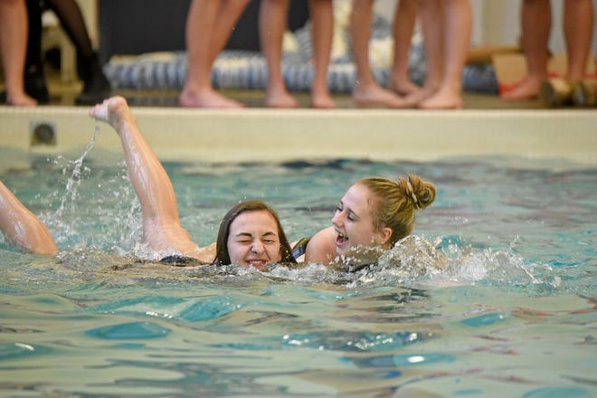Brooklyn Mills and Jacey Sermulis of Hillsdale Middle School sink with their ship Friday afternoon at the Mansfield Area Y during their cardboard boat races.