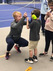 Former Lexington tennis star Katie (McCumiskey) Orlando, the director at Towpath Tennis Center in Akron, hangs a medal around the neck of one of the children involved in the ACEing Autism program she runs at the club.