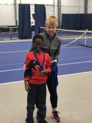 Former Lexington tennis star Katie (McCumiskey) Orlando, the director at Towpath Tennis Center in Akron, with one of the players in her ACEing Autism class at the club.