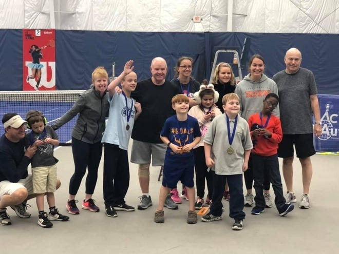 Former Lexington tennis star Katie (McCumiskey) Orlando, third from left, and her volunteer father, Bill, with the kids and other volunteers involved in the ACEing Autism program at Towpath Tennis Center in Akron, where Orlando is the director.