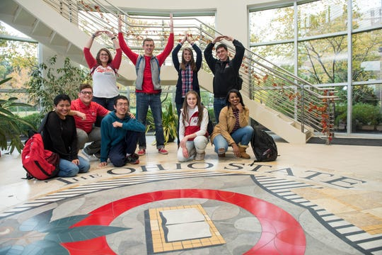 A group of students pose next to the university seal at the entrance of Maynard Hall.