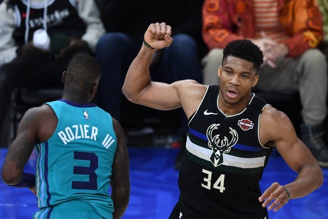Bucks forward Giannis Antetokounmpo reacts next to Hornets guard Terry Rozier after hitting a basket in Paris.