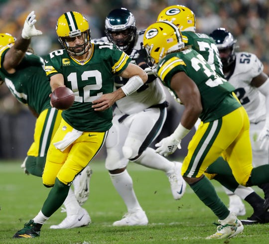 Packers quarterback Aaron Rodgers (12) hands off to Aaron Jones (33) against the Eagles on Sept. 26, 2019, at Lambeau Field.