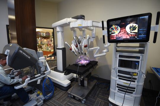 "A visitor tries to operate the da Vinci Xi surgical system on display at Baxter Regional Medical Center on Tuesday afternoon. The hospital recently purchased a da Vinci Xi system identical to the one displayed. The da Vinci systems are called ""medical robots,"" but they are not autonomous and require a human to control it."
