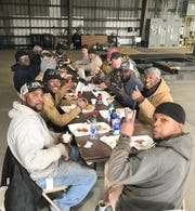 Epic Piping employees enjoy a fried fish lunch together during a midday break.