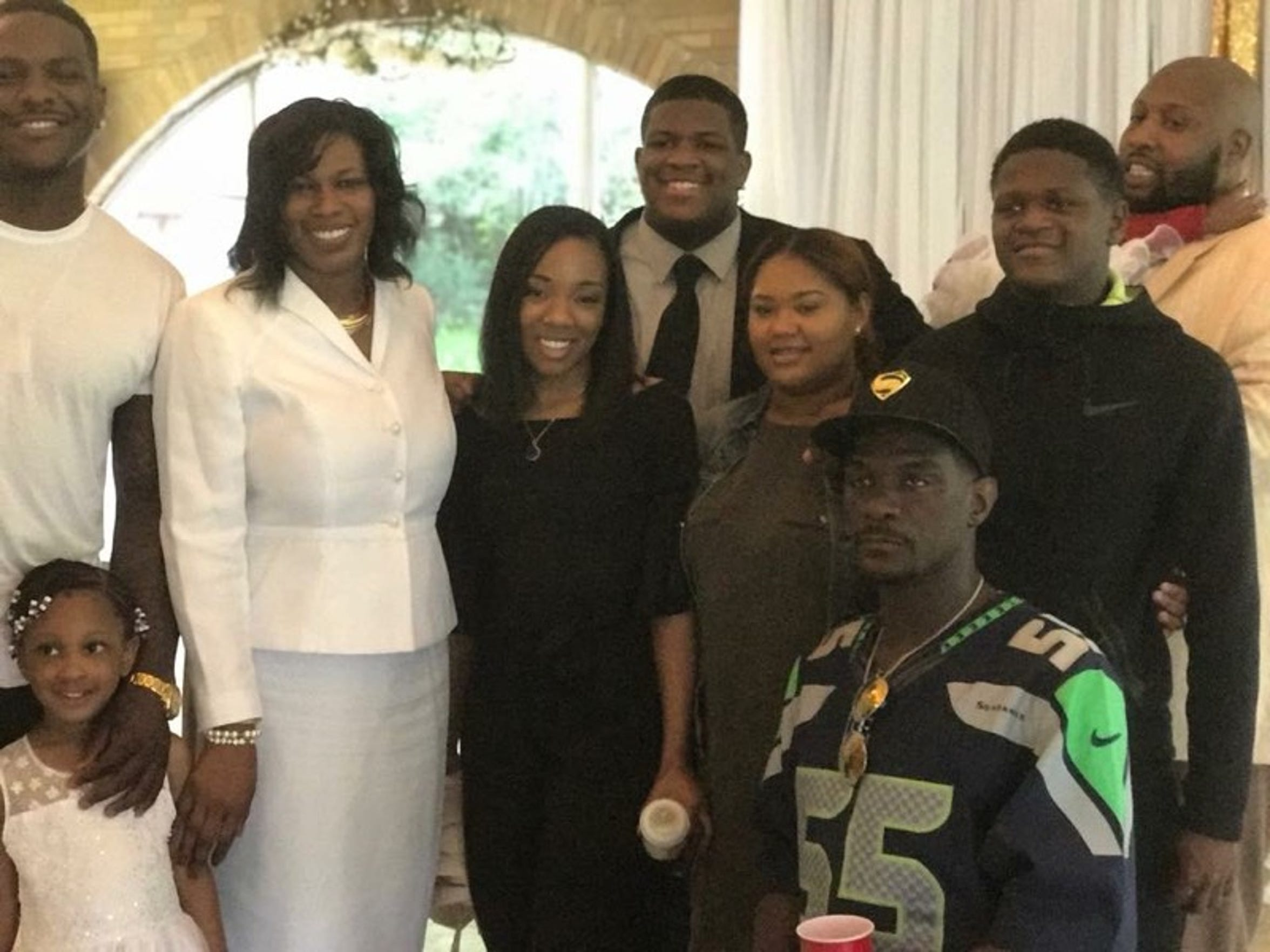 Frank Clark III (bottom right) poses in his son's Seattle Seahawks jersey (Frank Clark, left) while taking a photo with his family.