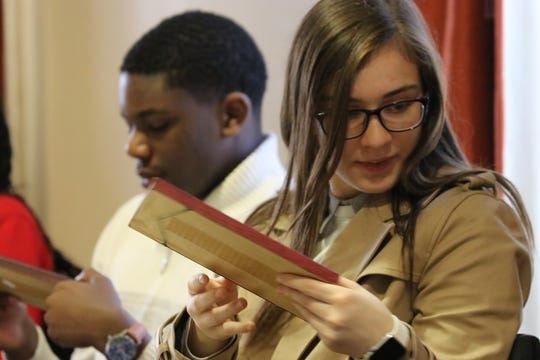 Aasiya Arif from Benjamin Franklin Middle School and Zachary Strickland from Thomas Jefferson Middle School look at souvenirs from trips the residents took.