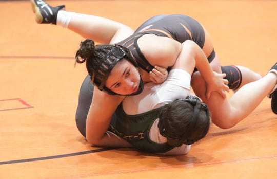 Aztec's Makayla Munoz holds down Los Alamos' Ivelyss Sandavol in the first round of the 126-pound division during Friday's New Mexico girls wrestling tournament at Lillywhite Gym in Aztec.