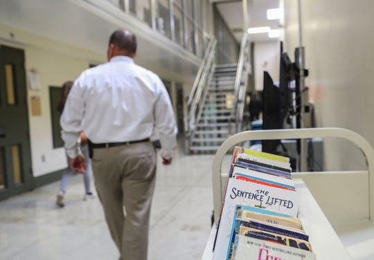 An ICE officer walks by a cart of books meant for detainees in the segregation unit at the U.S. Immigration and Customs Enforcement's Adelanto processing Center in Adelanto,Calif, on Dec. 3, 2019.