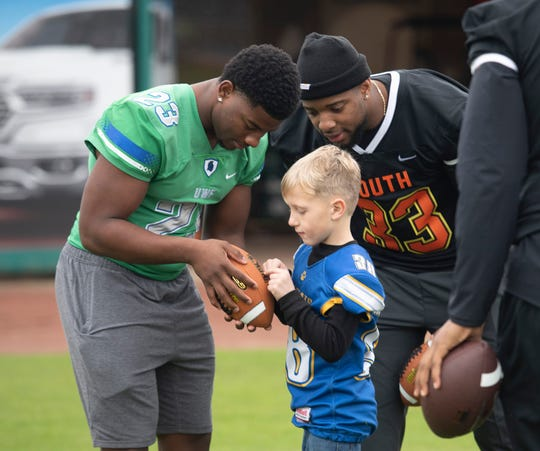 Forest Huxworth draws up a passing play with UWF's Onelio Rios and University of Alabam's Anfernee Jennings during a stop in Pensacola by the Senior Bowl Caravan on Friday, Jan.24, 2020.