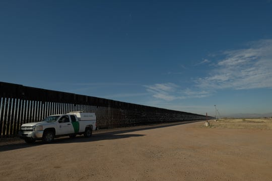 A Border Patrol agent parks beside 18-foot bollard-style fencing, built during the Bush administration, outside of Douglas on Jan. 8, 2020.