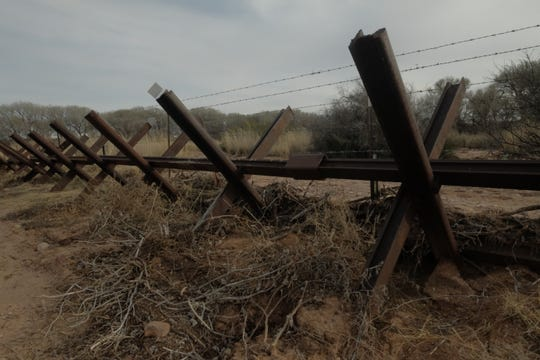 Debris builds up against Normandy-style vehicle barriers on the San Pedro River floodplain in southeast Arizona on Jan. 8, 2020.