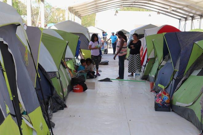 Grupos de personas, pertenecientes a la llamada caravana migrante, esperan para resolver su situación migratoria ayer jueves, en Matamoros, estado de Tamaulipas (México).