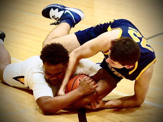 Port Huron Northern's Tyler Jamison fights for a loose ball against Sterling Heights during a Macomb Area Conference-Gold boys basketball game on Thursday, Jan. 23, 2020.