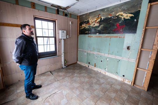 Dennis Delor, special events, marketing and volunteer coordinator for the St. Clair County Parks & Recreation Commission, stands next to a mural that was discovered beneath wall paneling in the former radio room of the U.S. Coast Guard building at Fort Gratiot Light Station Friday, Jan. 24, 2020. The mural is believed to be from the 1950's or '60s, and was found during restoration work on the building.