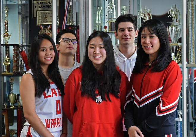 Excel Christian School student athletes pose for a photo in front of the school's trophy case on Jan. 24, 2020. Front row left to right is, Nutnicha Jutanmas of Thailand plays volleyball and basketball, Eunseon Jung of Korea plays basketball, Narapat Jutamas of Thailand plays basketball and cheer. In the back row is Yanrui Sun, left, of China plays basketball and Berke Arslankara of Turkey plays football and basketball.