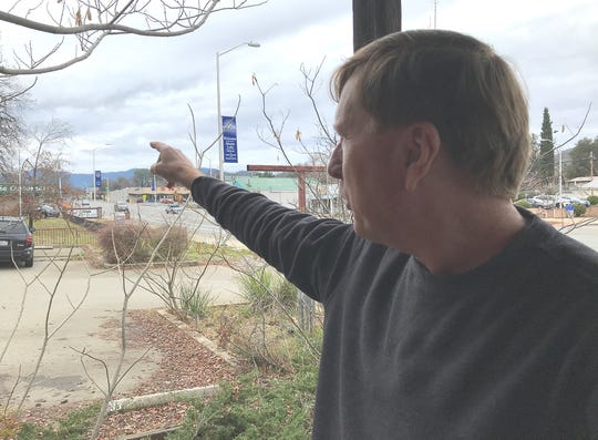 "Bob Nelson, owner of Central Valley Feed, points to an area where K2 Development wants to build a residential-commercial center called Boomtown in Shasta Lake. Nelson's store is next to the proposed development. ""The new project has a good possibility to vitalize the city,"" he said."