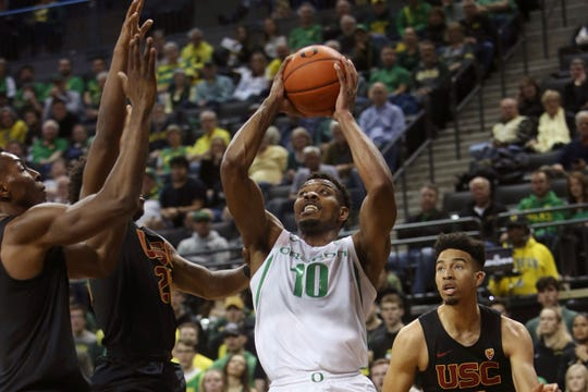 Oregon's Shakur Juiston, center, goes up for a shot against Southern California's Onyeka Okongwu, left, Ethan Anderson and Isaiah Mobley, right, during the first half of an NCAA basketball game in Eugene, Ore., Thursday, Jan. 23, 2020.