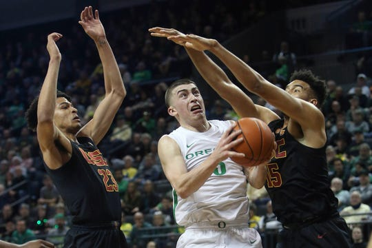 Oregon's Payton Pritchard, center, goes up for a shot between Southern California's Max Agbonkpolo, left, and Isaiah Mobley, right, during the first half of an NCAA basketball game in Eugene, Ore., Thursday, Jan. 23, 2020.