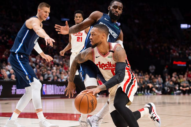 Portland Trail Blazers guard Damian Lillard (0) drives to the basket during the first half against Dallas Mavericks guard Tim Hardaway Jr. (11) at Moda Center.