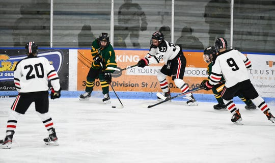 Luke Johnson (37), August Falloon (20) and Blake Keller (9) of St. Cloud surround Easton Portner of Sauk Rapids during the first period Thursday, Jan. 23, 2020, at the MAC in St. Cloud.