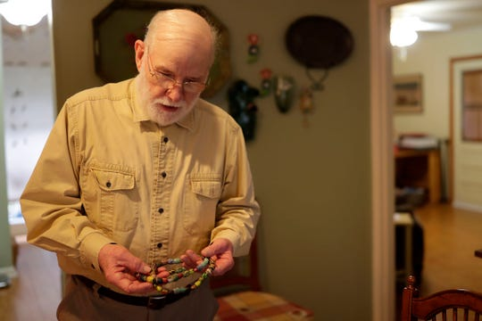 Kermit Brown holds a necklace he designed with polymer clay beads that he created during his retirement.