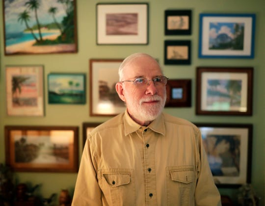Kermit Brown stands in front a wall in his home covered in frames that he built during his 25 years of retirement.