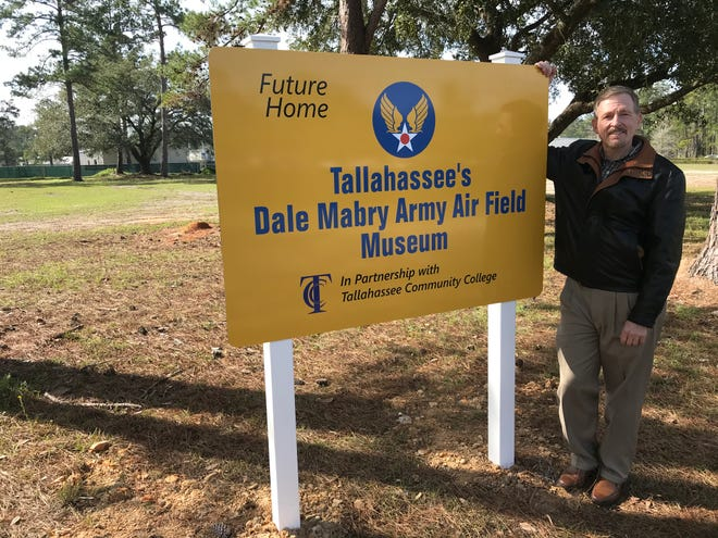 Chuck Wells, chair of Tallahassee's Dale Mabry Air Field Museum, Inc. board, stands next to sign designating area where the planned museum will be built on the campus of Tallahassee Community College.