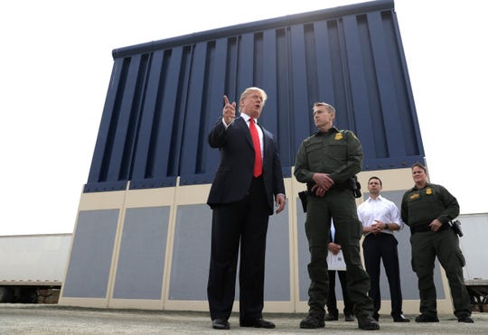 In this March 13, 2018, file photo, President Donald Trump speaks as he reviews border wall prototypes in San Diego, California, as Rodney Scott, the Border Patrol's new chief, listens.