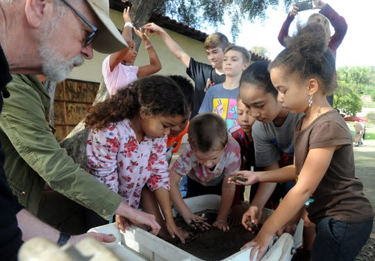 """Archaeologist John Foster shows children excavation techniques on Friday, Jan. 24, 2020, at the Albinger Archaeological Museum in Ventura. The museum is hosting """"Dig into History"""" this weekend to celebrate its 40th anniversary."""