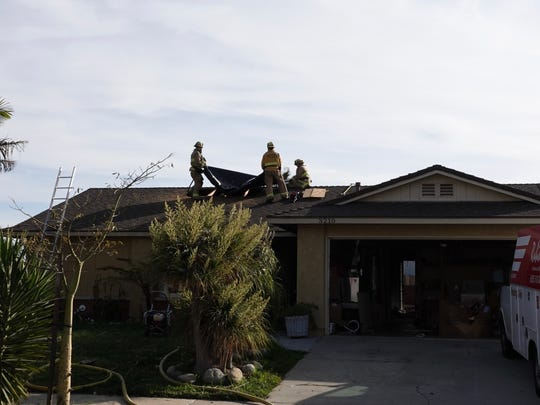 Firefighters cover a portion of the roof of a house on Net Street in Oxnard after a fire broke out in the attic Friday afternoon. A woman and two children were displaced because of the damage.